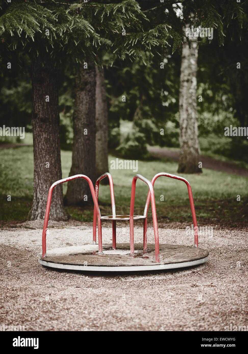 Leeren Sie Kinderkarussell auf dem Spielplatz, unheimliche Gefühl, Kreuz bearbeitetes Bild Stockbild