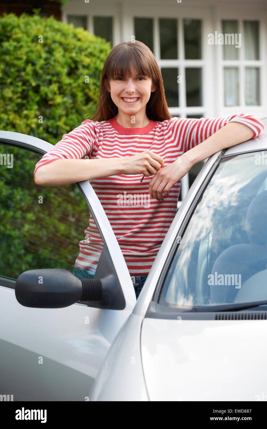 Lächelnde junge Frau stand neben dem Auto Stockfoto