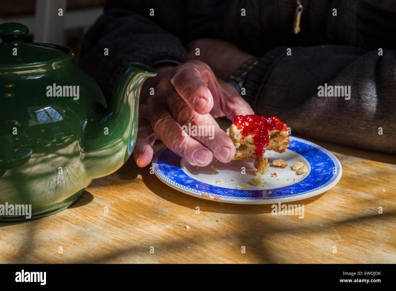 Hand von Rentner Essen britische Sahne Tee Stockbild
