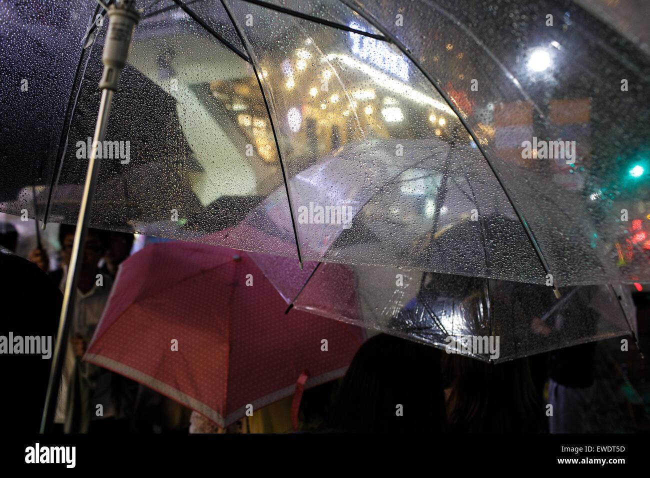 Menschen mit Regenschirmen im Regen in Shibuya in der Nacht in Tokio, Japan Stockbild
