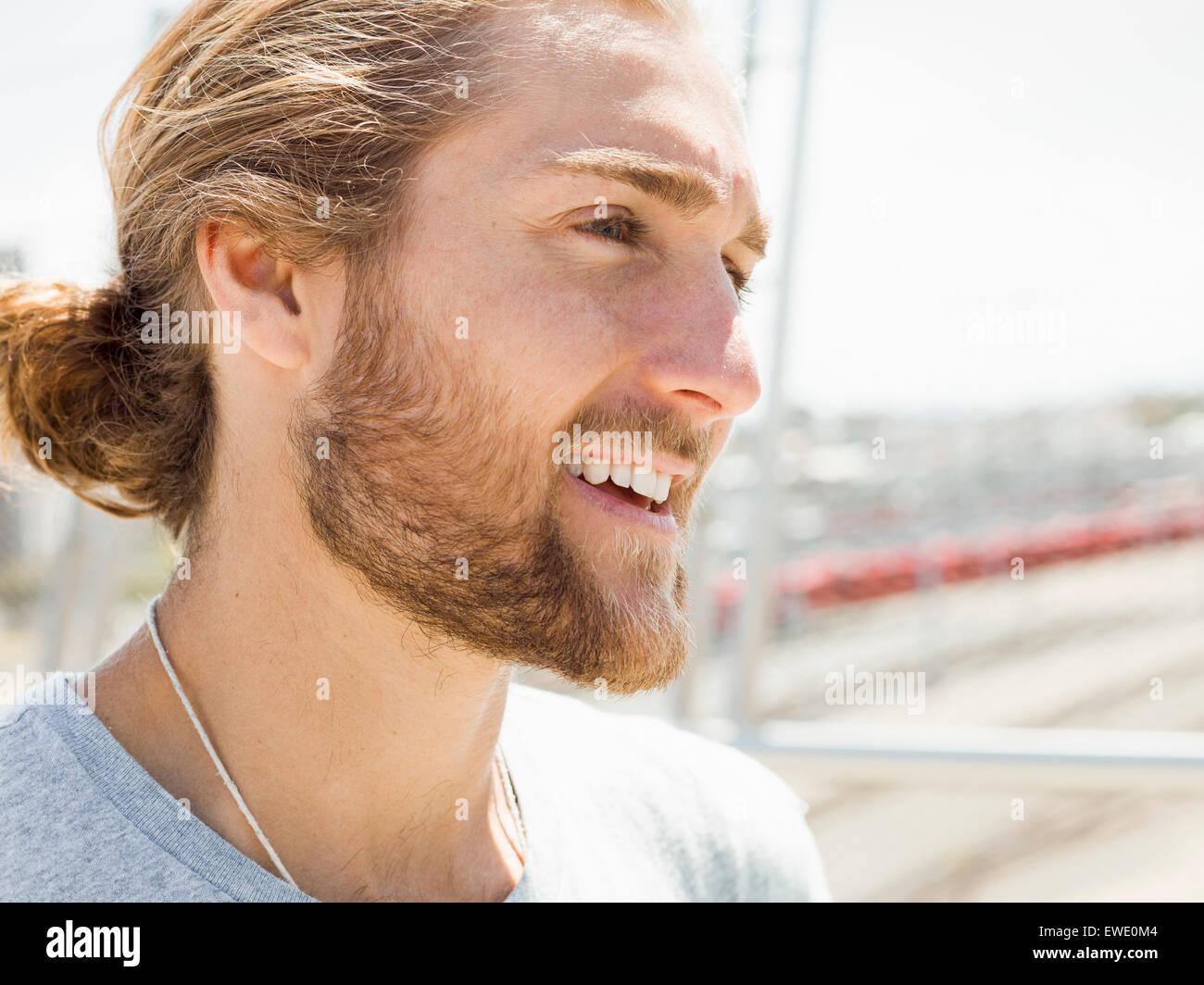 Ein junger Mann mit Bart, rote Haare und Pferdeschwanz Stockbild