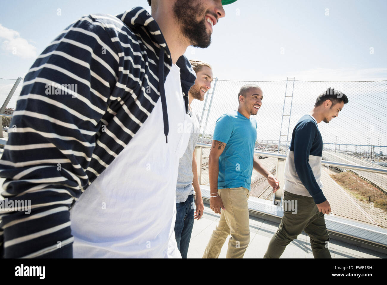 Gruppe junger Männer zu Fuß entlang der Fußgängerbrücke Stockbild