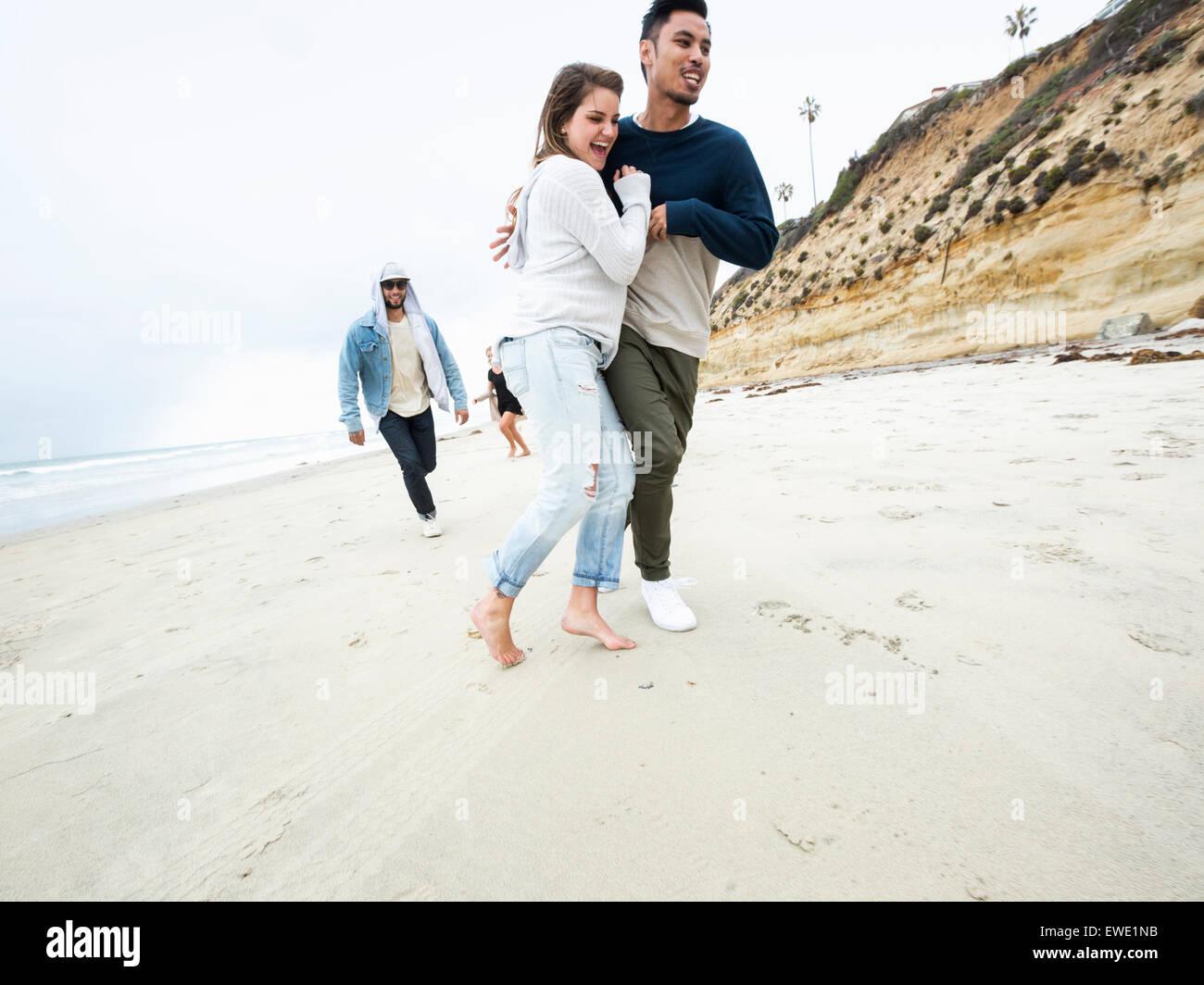 Eine Gruppe junger Männer und Frauen laufen am Strand, Spaß Stockbild