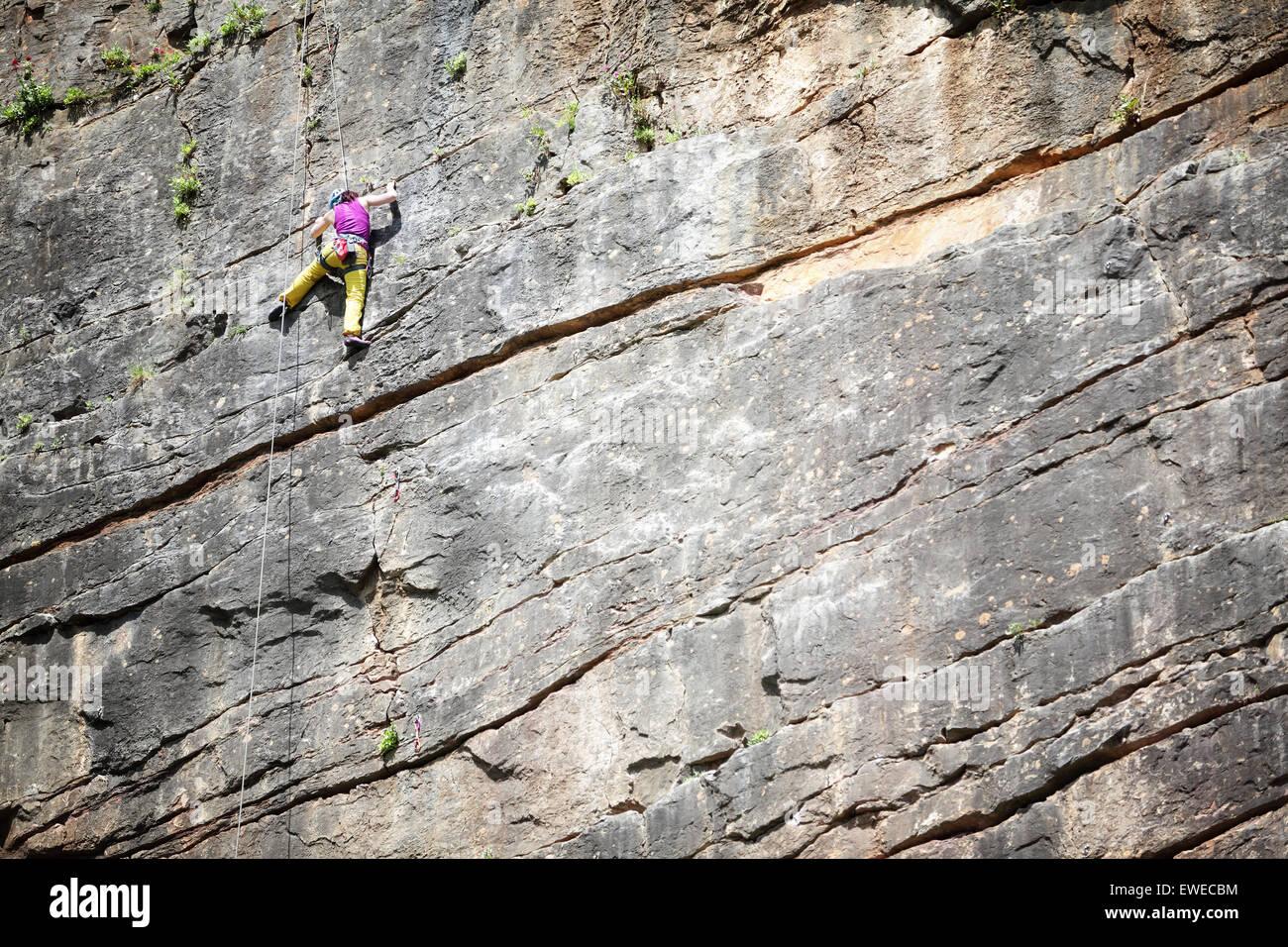 Stretching für Kletterer halten auf vertikalen Aufstieg mit Textfreiraum Stockbild