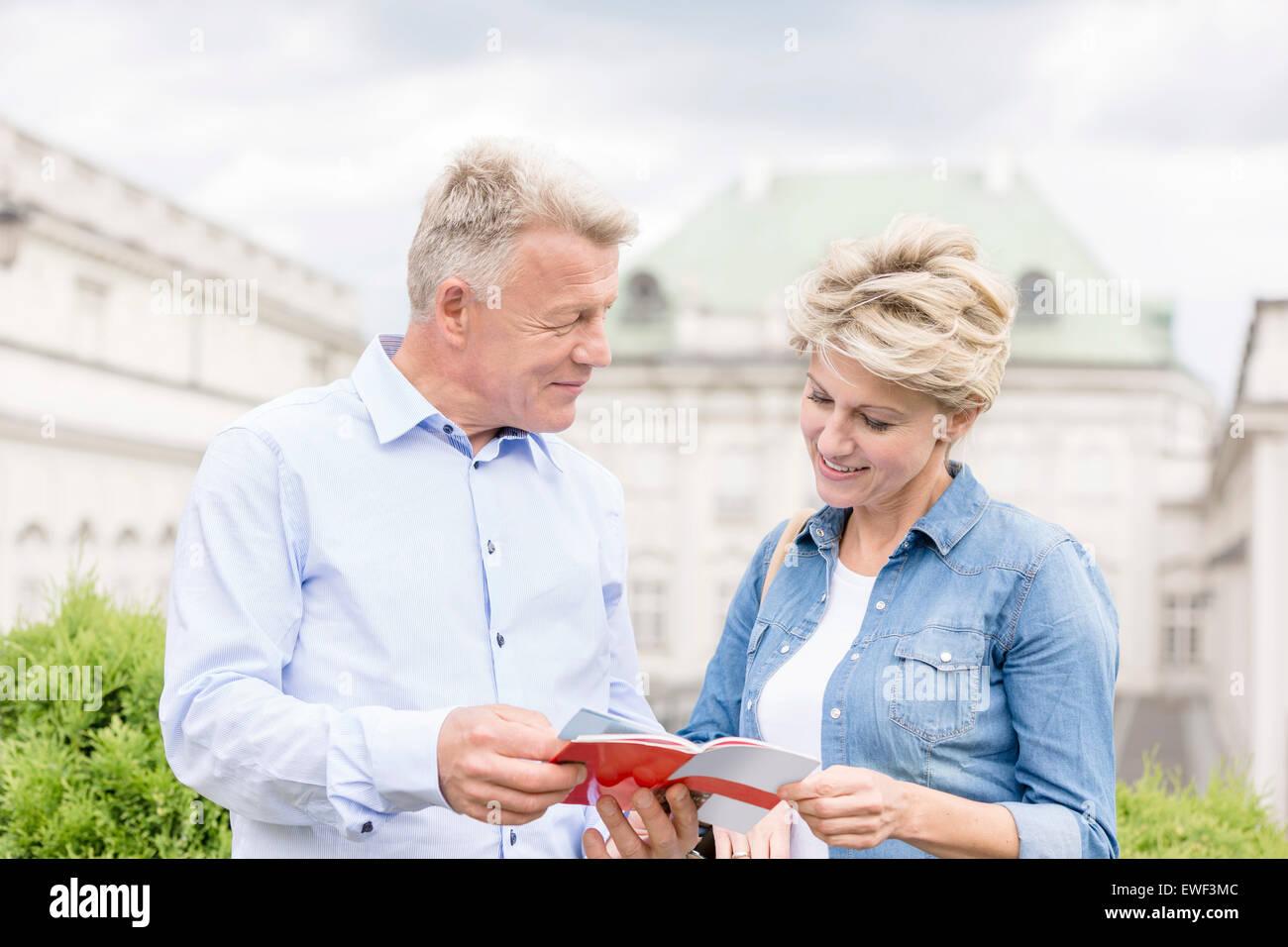 Paar mittleren Alters lesen Ratgeber außerhalb Gebäude Stockbild