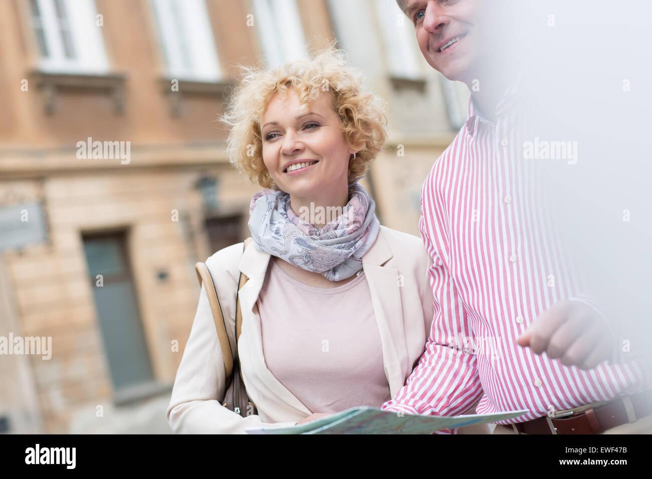 Glückliches Paar mittleren Alters mit Karte in der Stadt Stockbild