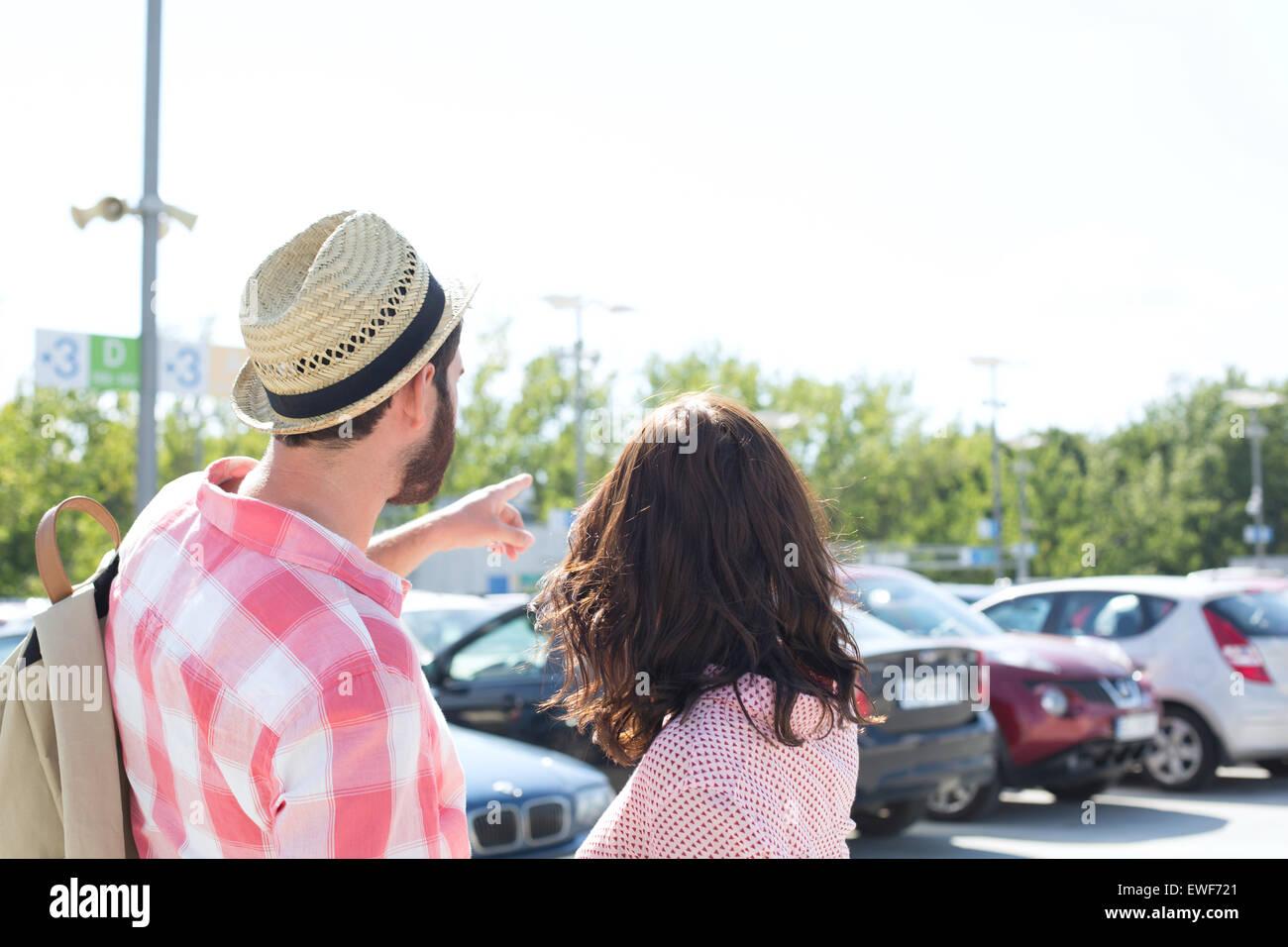 Mann etwas zu Frau auf Stadt Straße gegen klaren Himmel zeigen Stockbild