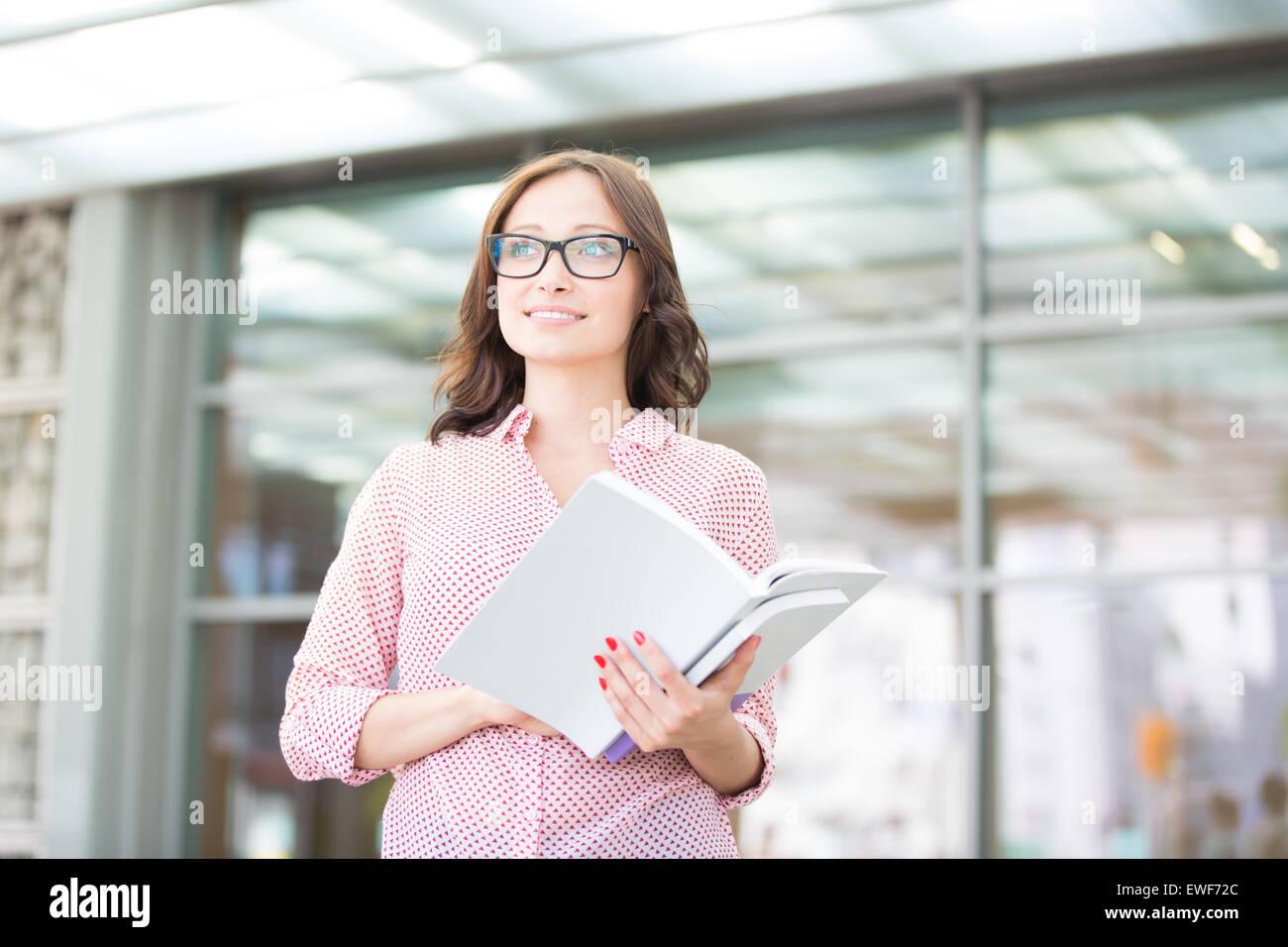 Lächelnde Frau wegsehen außerhalb Gebäude mit gedrückter Stockbild