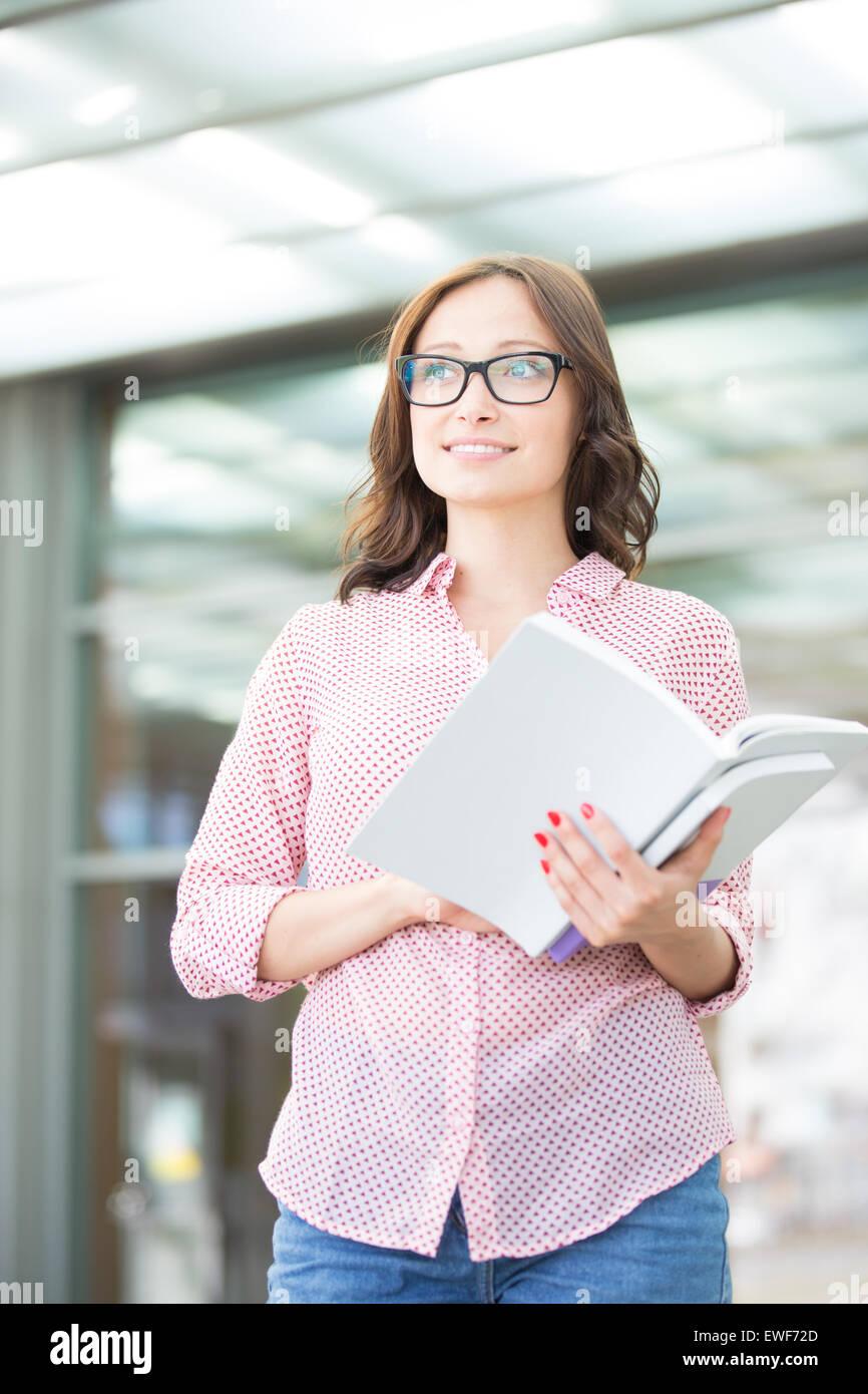 Nachdenkliche Frau wegsehen Buch draußen halten Stockbild