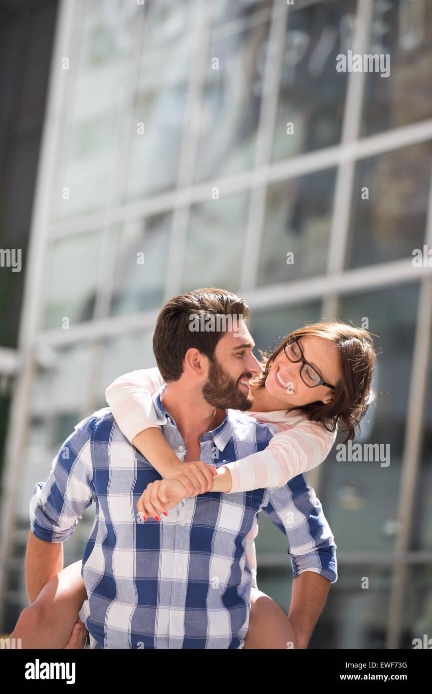 Glückliches Paar sahen einander genießen Huckepack fahren in Stadt Stockbild