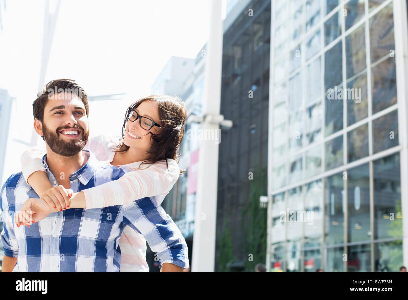 Glücklicher Mann geben Huckepack Fahrt zur Frau in der Stadt Stockfoto