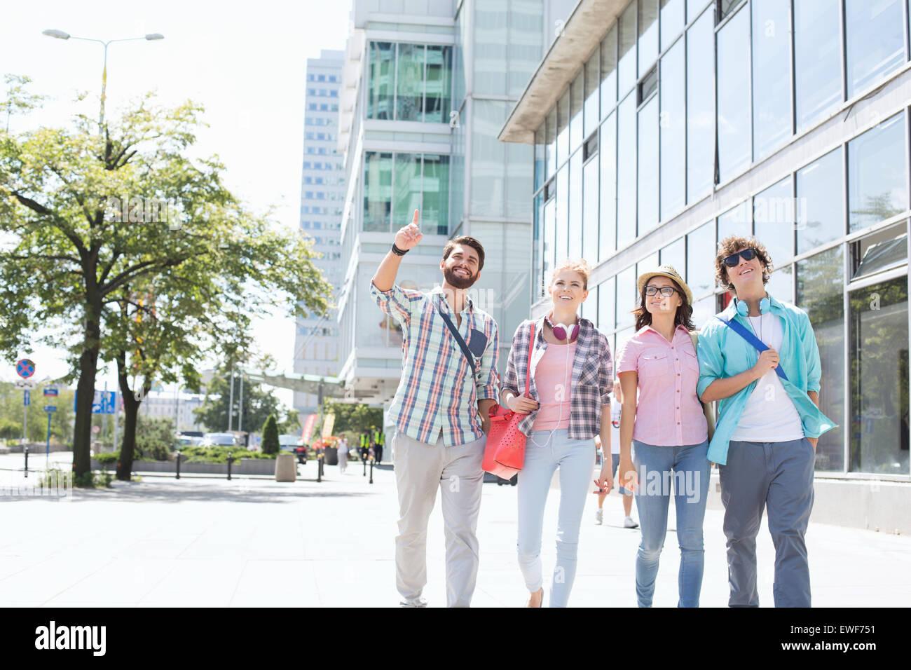 Glücklicher Mann zeigen etwas an Freunde während des Gehens in Stadt Stockfoto