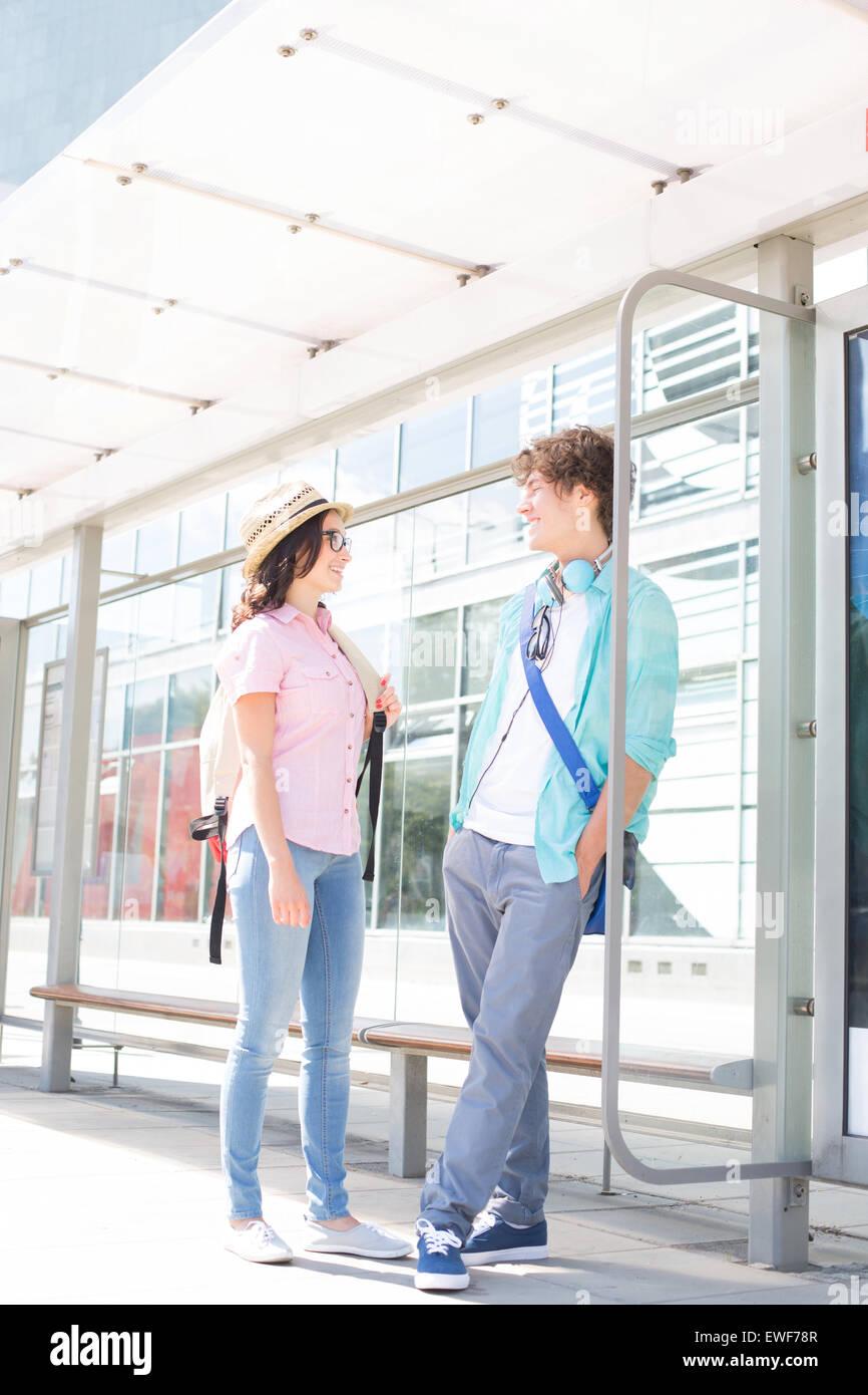 Paar beim warten an der Bushaltestelle zu kommunizieren Stockbild