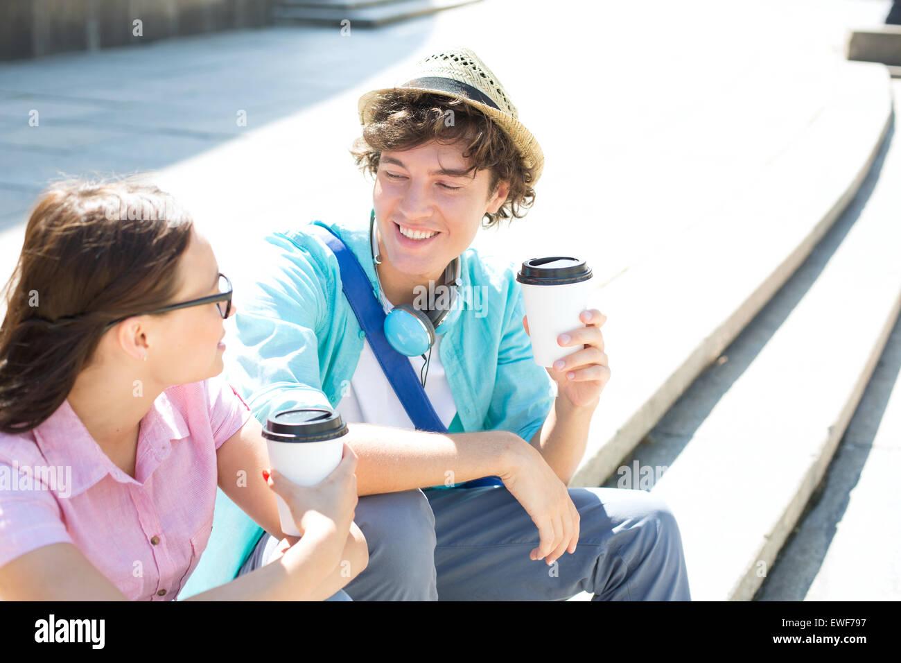 Glückliche Freunde halten Einweg Kaffeetassen auf Schritte im freien sitzend Stockfoto