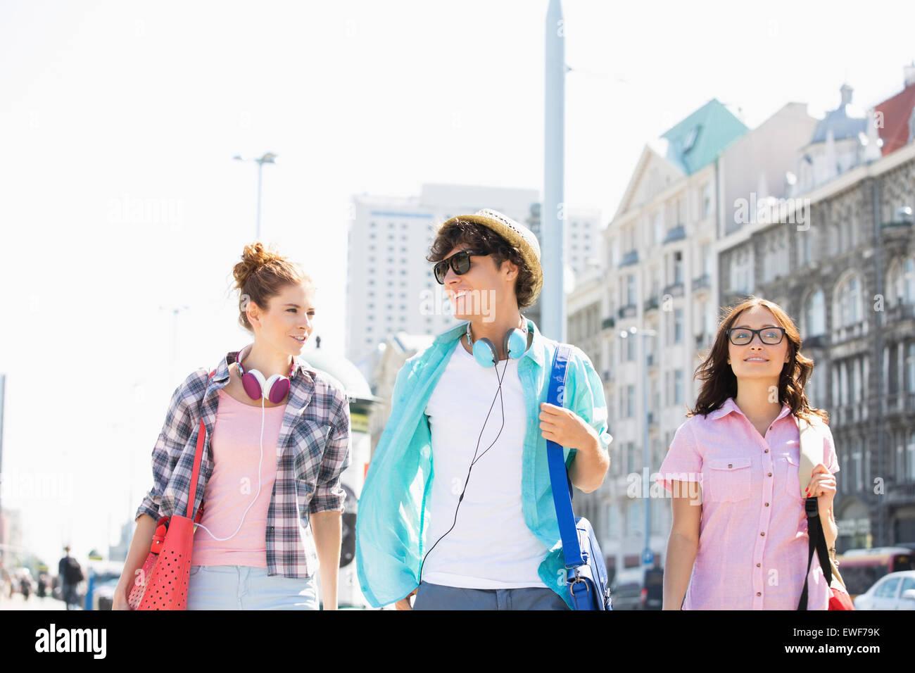 Glückliche Freunde sprechen während des Gehens in Stadt Stockbild