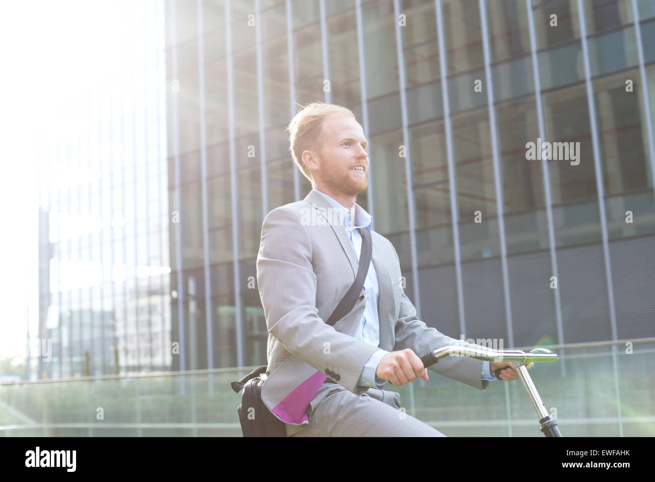Geschäftsmann Reiten Fahrrad vor Bürogebäude Stockfoto