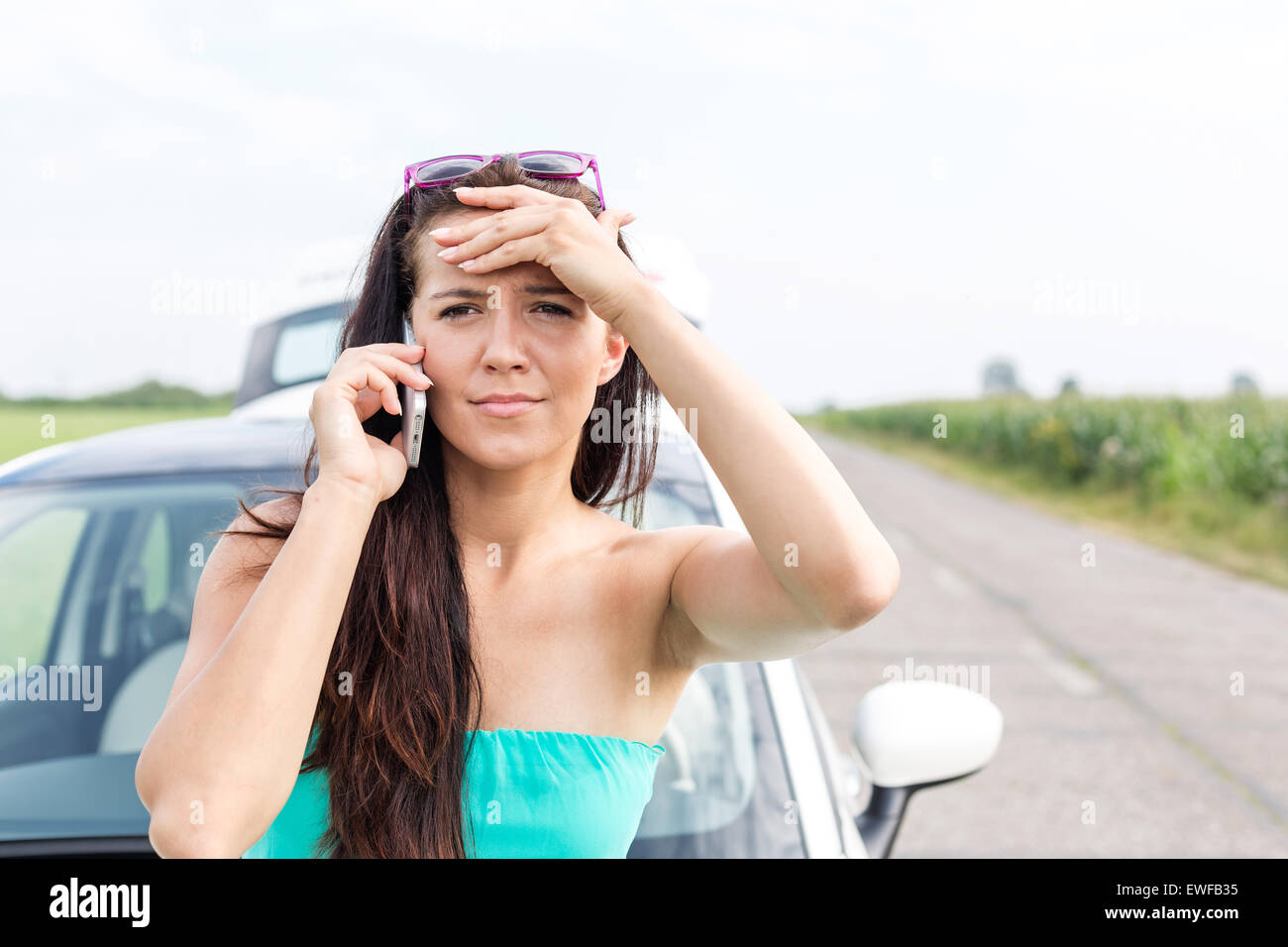 Porträt des gespannten Frau mit Handy gegen aufgeschlüsselt Auto unterwegs Stockbild