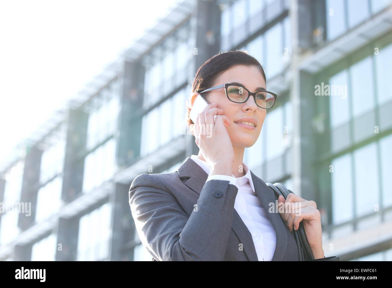 Niedrigen Winkel Ansicht der Geschäftsfrau mit Handy vor Bürogebäude Stockfoto