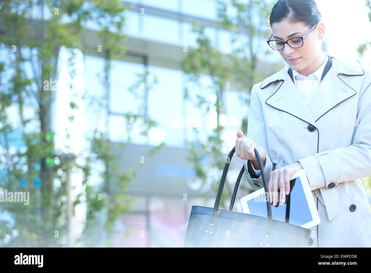 Geschäftsfrau, die digital-Tablette ins Portemonnaie im freien Stockbild