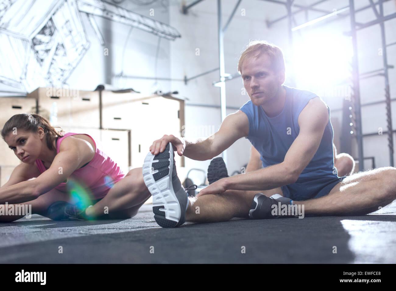 Zuversichtlich, dass Mann und Frau dabei dehnen im Crossfit Fitnessstudio trainieren Stockbild