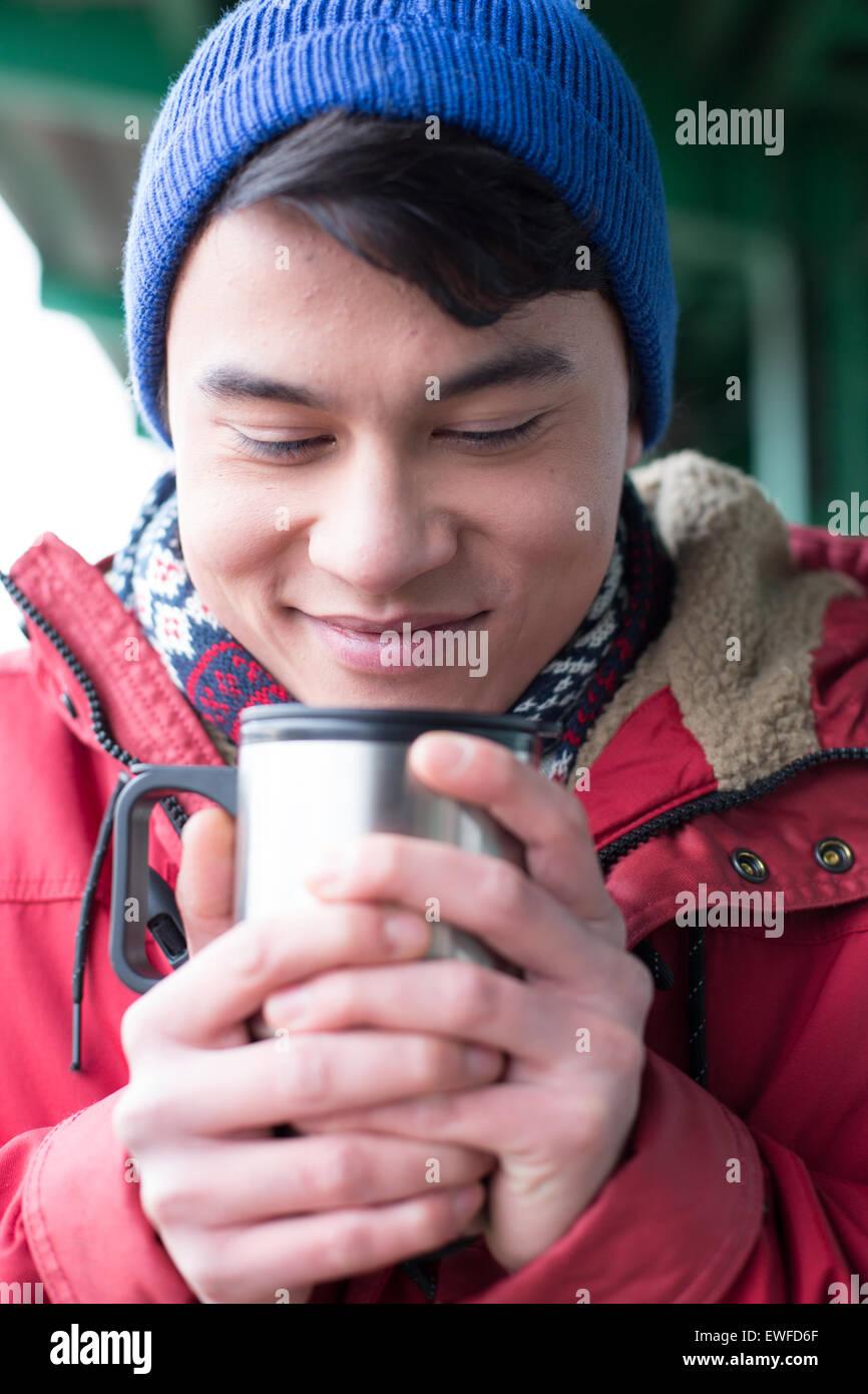 Lächelnder Mann betrachtet man Kaffee in isolierten Getränkeverpackung im winter Stockbild