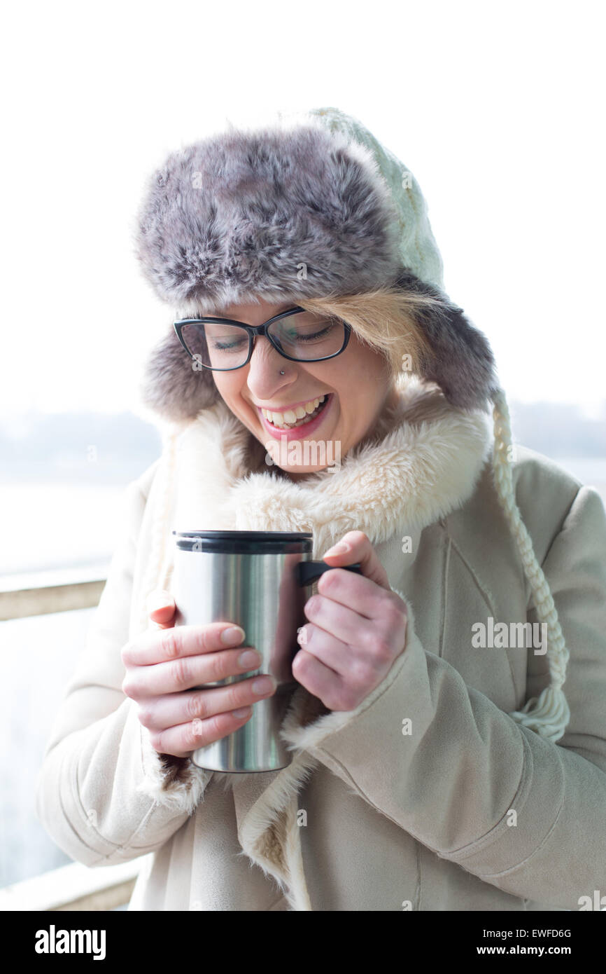 Stets gut gelaunte Frau in warme Kleidung mit isolierten Getränkeverpackung Stockbild