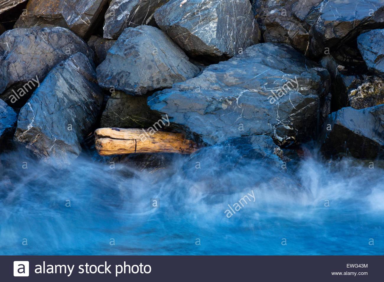 Wellen von Puget Sound Absturz gegen Treibholz in einem Wellenbrecher in Edmonds, Washington stecken. Stockbild