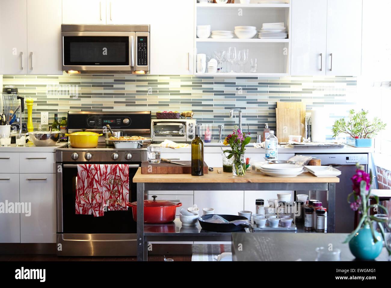 moderne Küche gelben Topf roten Handtuch modernen Geräten weiße Küchenschränke Glas zurück Stockbild