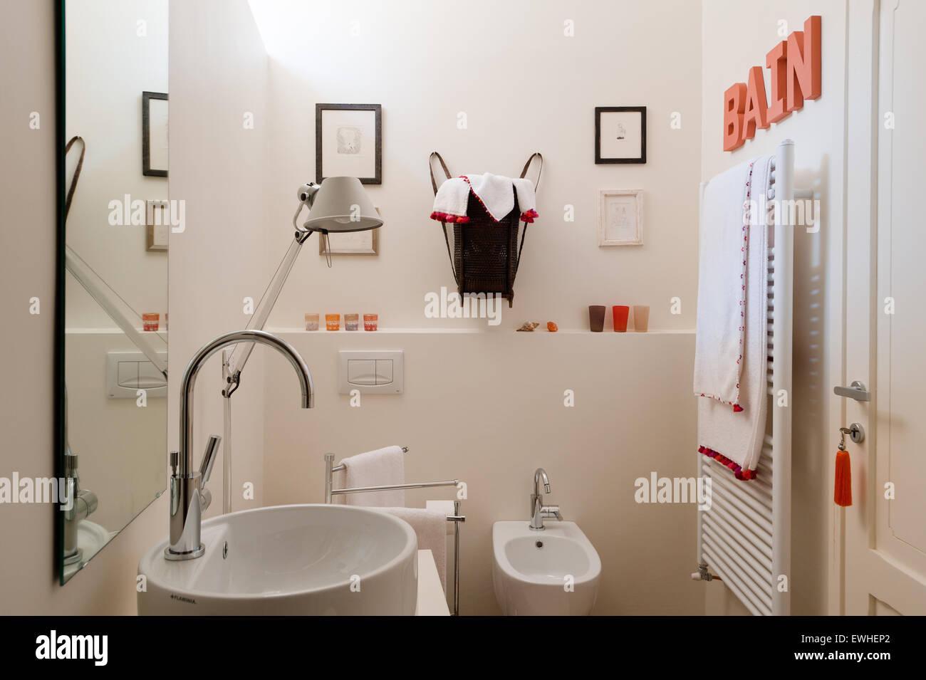 Helles Modernes Bad Mit Beheiztem Handtuchhalter, Bunte Schriftzüge Und  Lampe Von Artemide