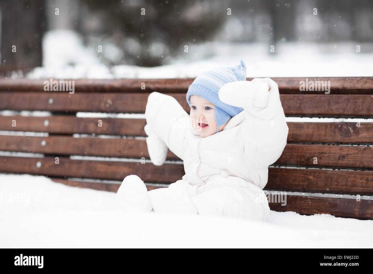s e lustige baby sitzen auf einer bank in einem park an einem verschneiten wintertag stockfoto. Black Bedroom Furniture Sets. Home Design Ideas