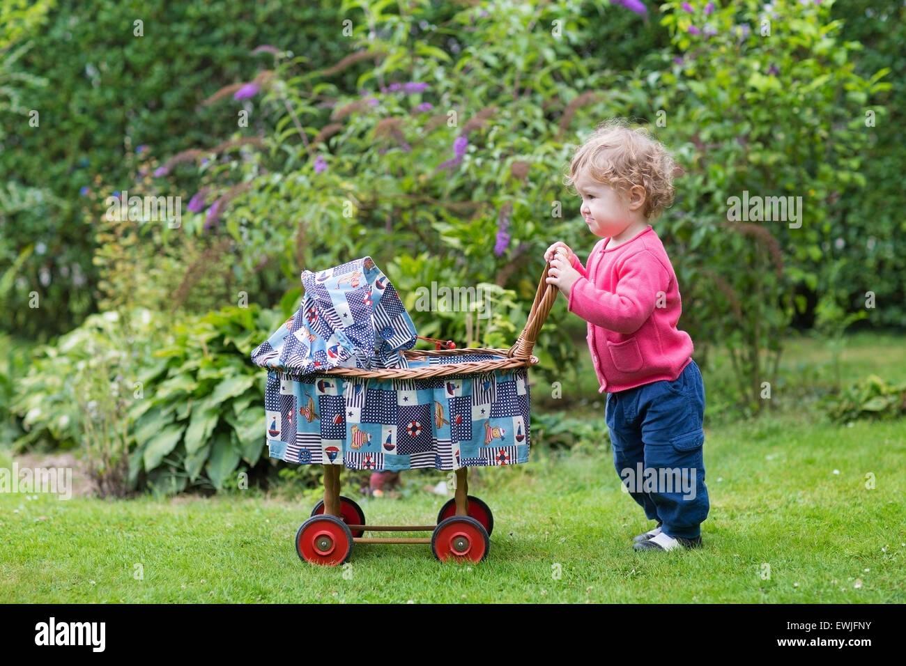 lustige lockiges babym dchen spielen mit einem vintage puppe kinderwagen im garten stockfoto. Black Bedroom Furniture Sets. Home Design Ideas