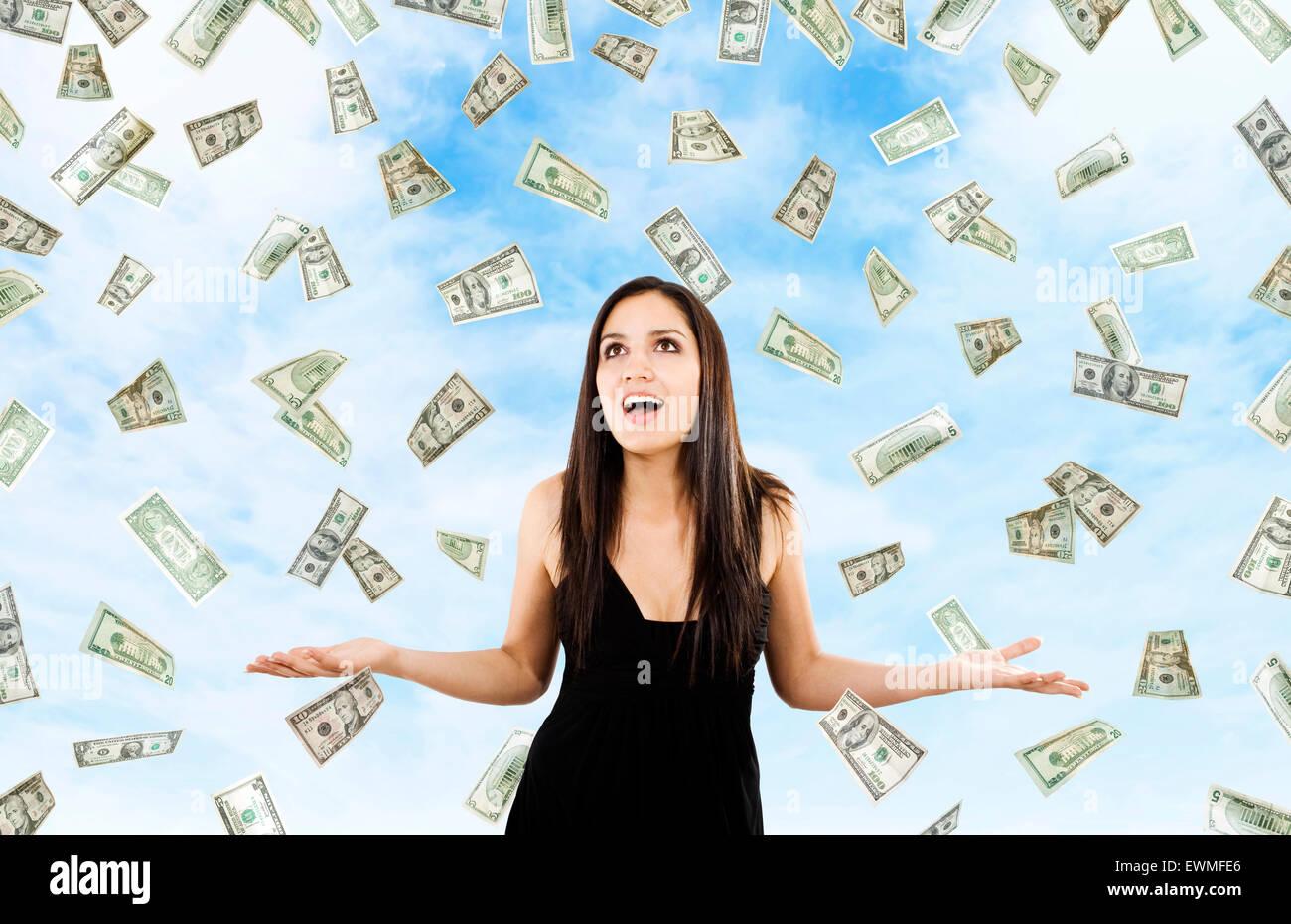 Bild der Frau, die mit offenen Armen inmitten fallenden Geld Stockfoto