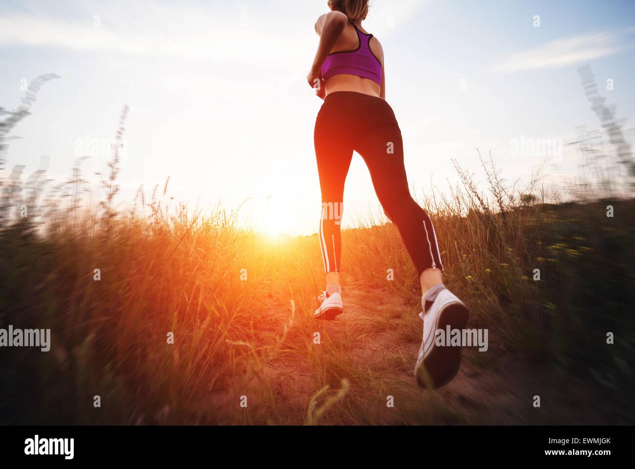 Junge Frau läuft auf einer Landstraße bei Sonnenuntergang in Sommerwiese. Lifestyle-Sport-Hintergrund Stockfoto