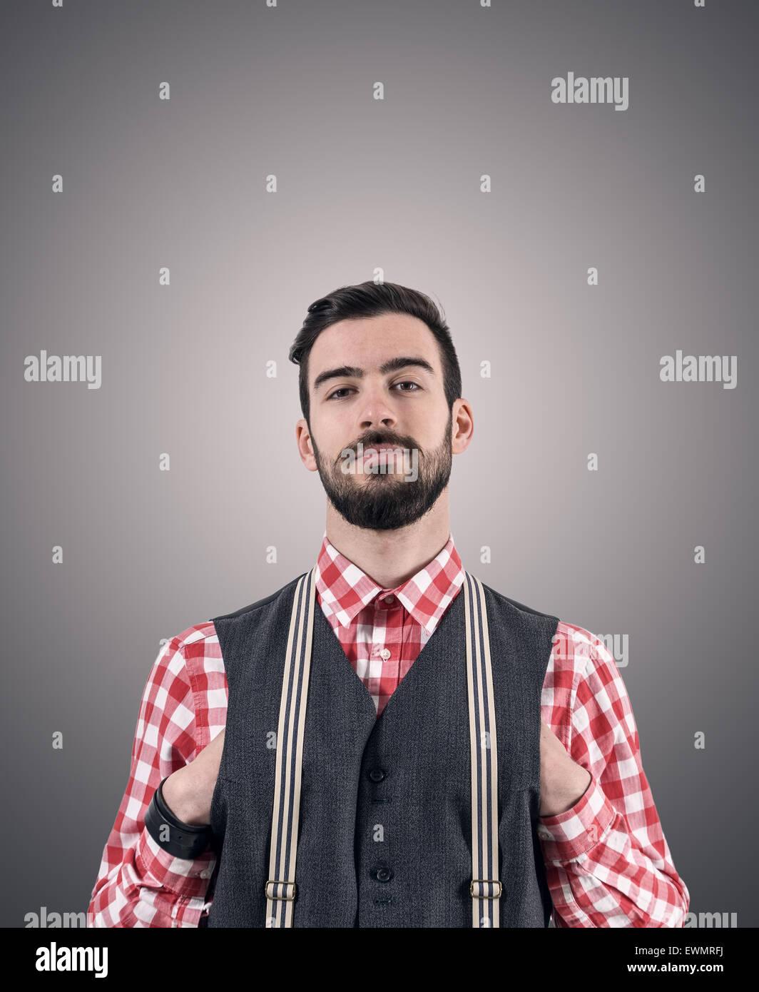 Entsättigt Porträt der junge bärtige Hipster mit Händen schob in seiner Weste über dunkle Stockbild