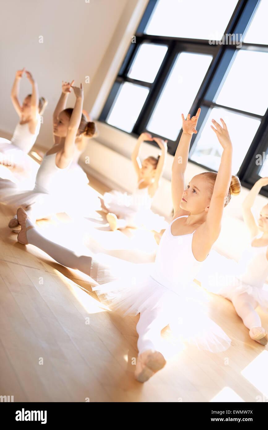 Niedliche Junge Ballett-Mädchen in einer Übung mit offenen Beinen und Arme nach oben beim Sitzen auf dem Stockbild