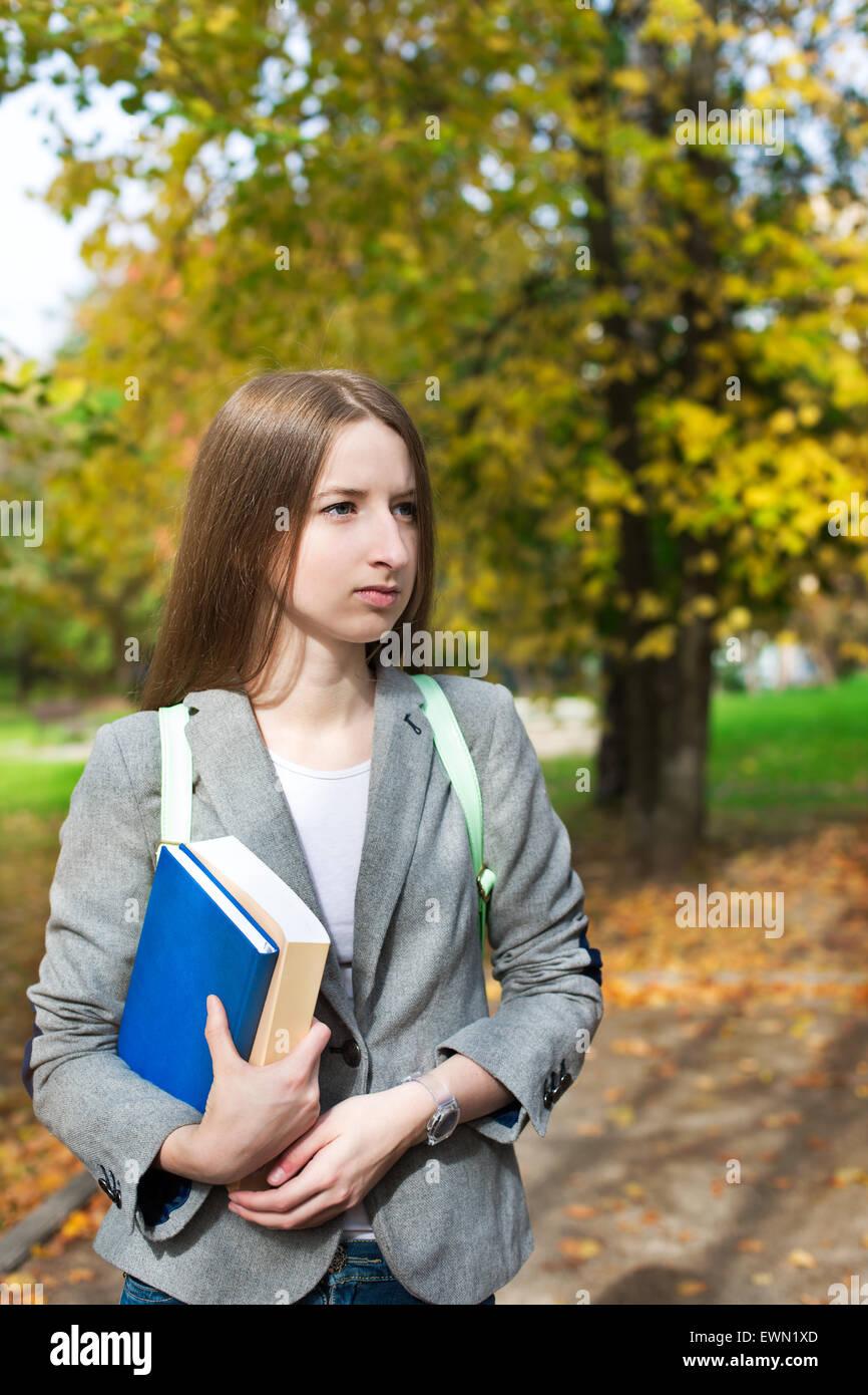 Student mit Buch stand in der Nähe der Herbst Bäume Stockbild