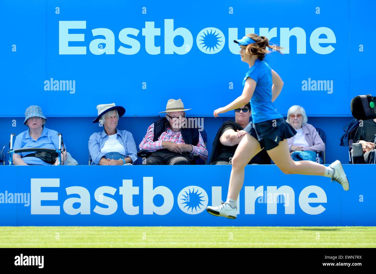Ältere Zuschauer und eine laufende Ballmädchen auf dem Centrecourt bei den Aegon International Turnier Stockbild