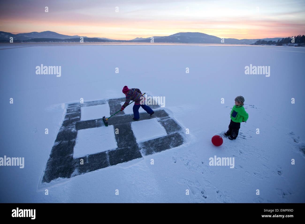 Ein kleines Mädchen bereitet einen viereckigen Hof auf dem Eis während ein anderer Uhren Winzling. Stockbild