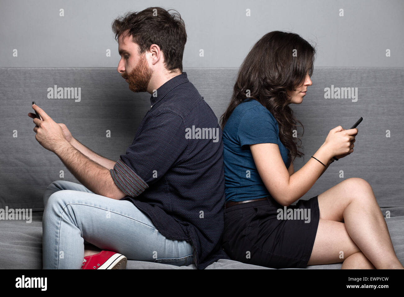 Junge Stille paar mit Smartphones, die auf einer Couch sitzend Stockfoto
