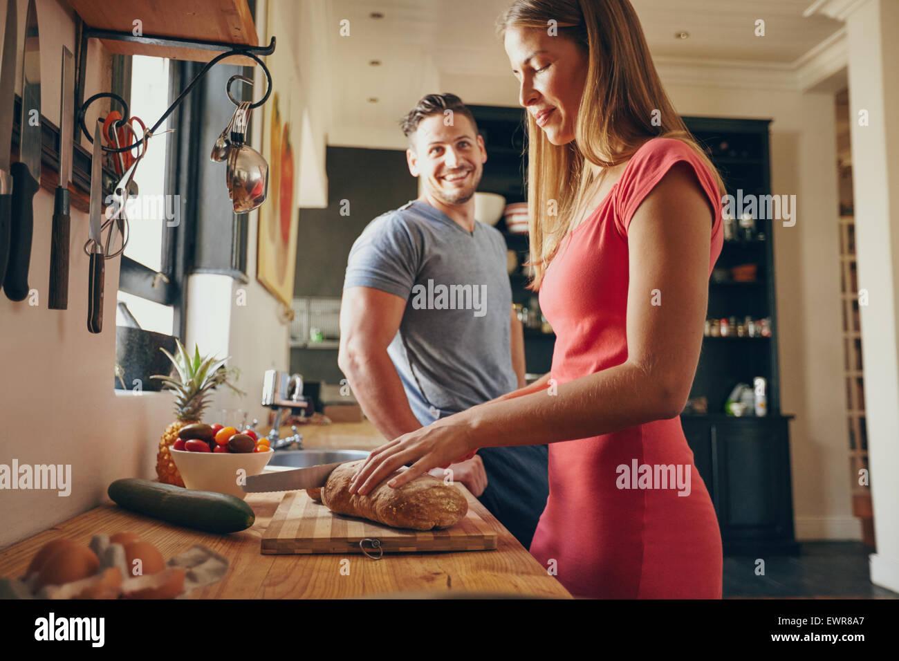 Innenaufnahme der junge Mann und Frau in der Küche am Morgen. Konzentrieren Sie sich auf Frau Schneiden von Stockbild