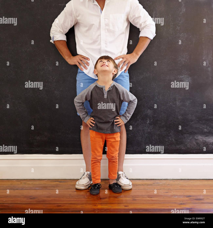 Innenaufnahme des kleinen Jungen Blick auf seinen Vater beim stehen vorne mit den Händen auf Taille. Stockbild