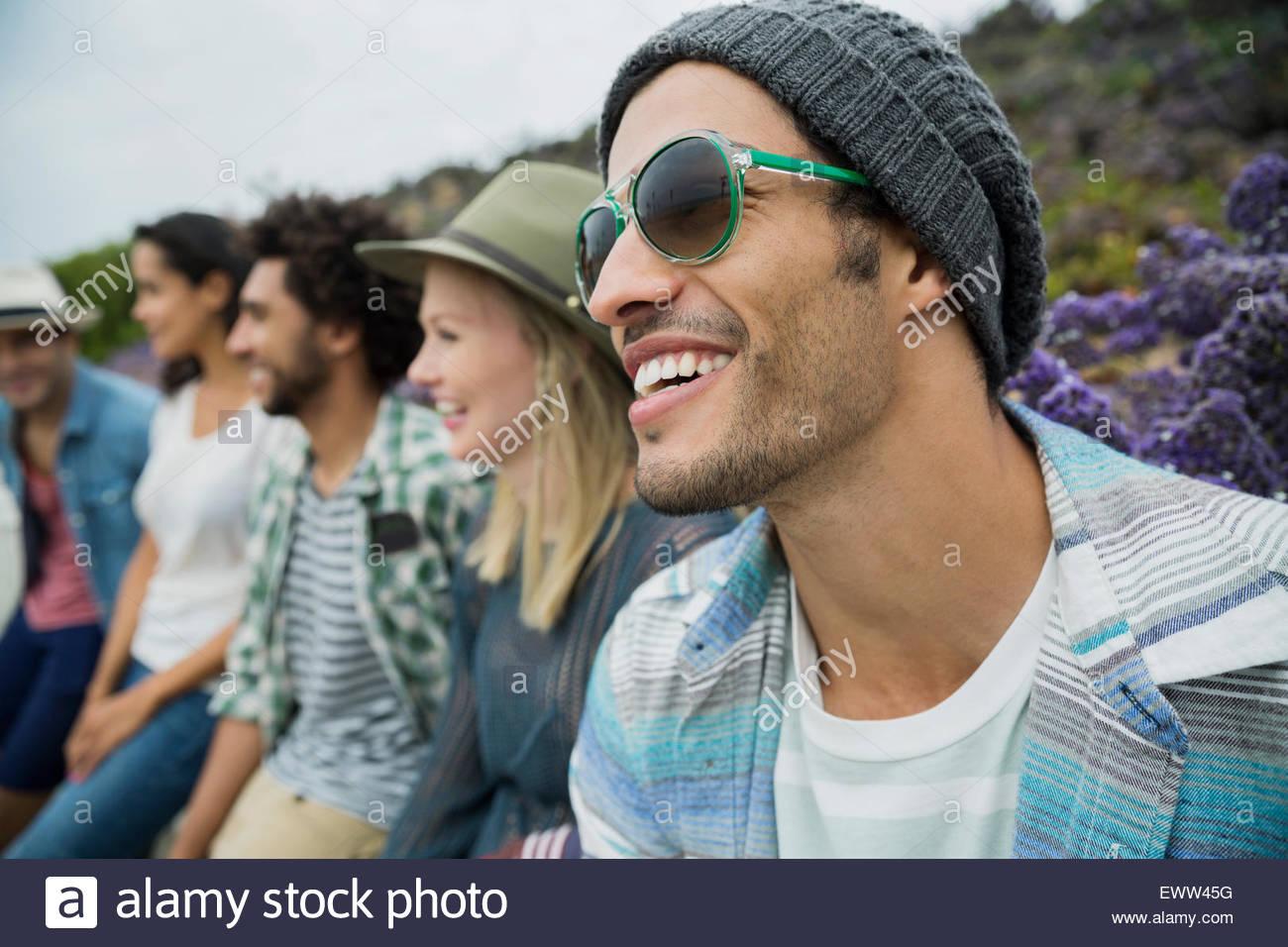 Lächelnden Freunde sitzen in einer Reihe Stockbild
