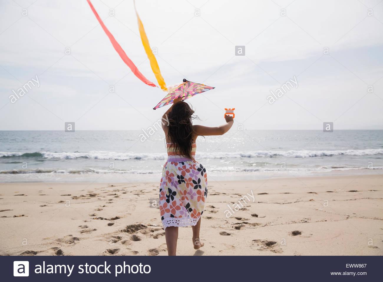 Mädchen im Kleid Drachen am Sonnenstrand Stockbild