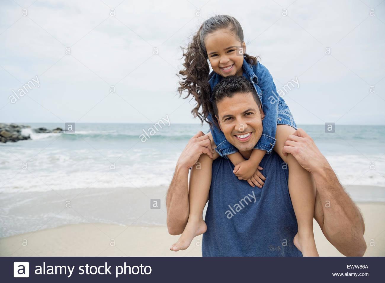 Porträt lächelnden Vater Tochter am Strand von Schultern tragen Stockbild