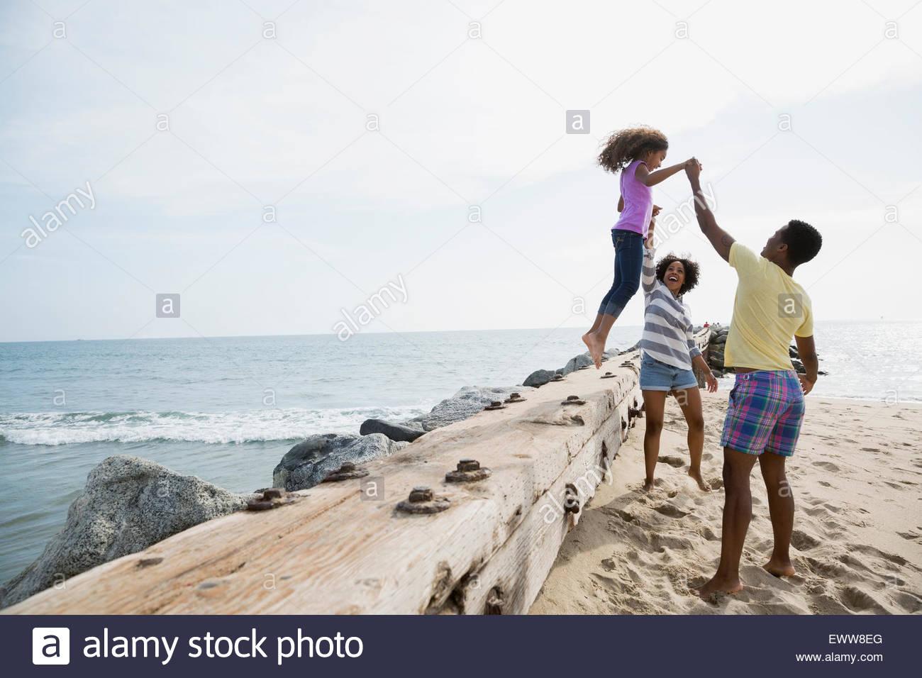 Vater und Mutter Tochter Sprung Strand Wand zu helfen Stockbild