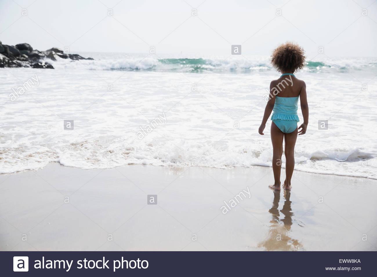 Mädchen im Badeanzug Blick auf Ozeanstrand Stockbild