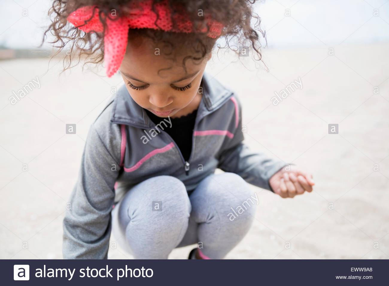 Mädchen mit dem lockigen Haar hocken am Strand Stockbild
