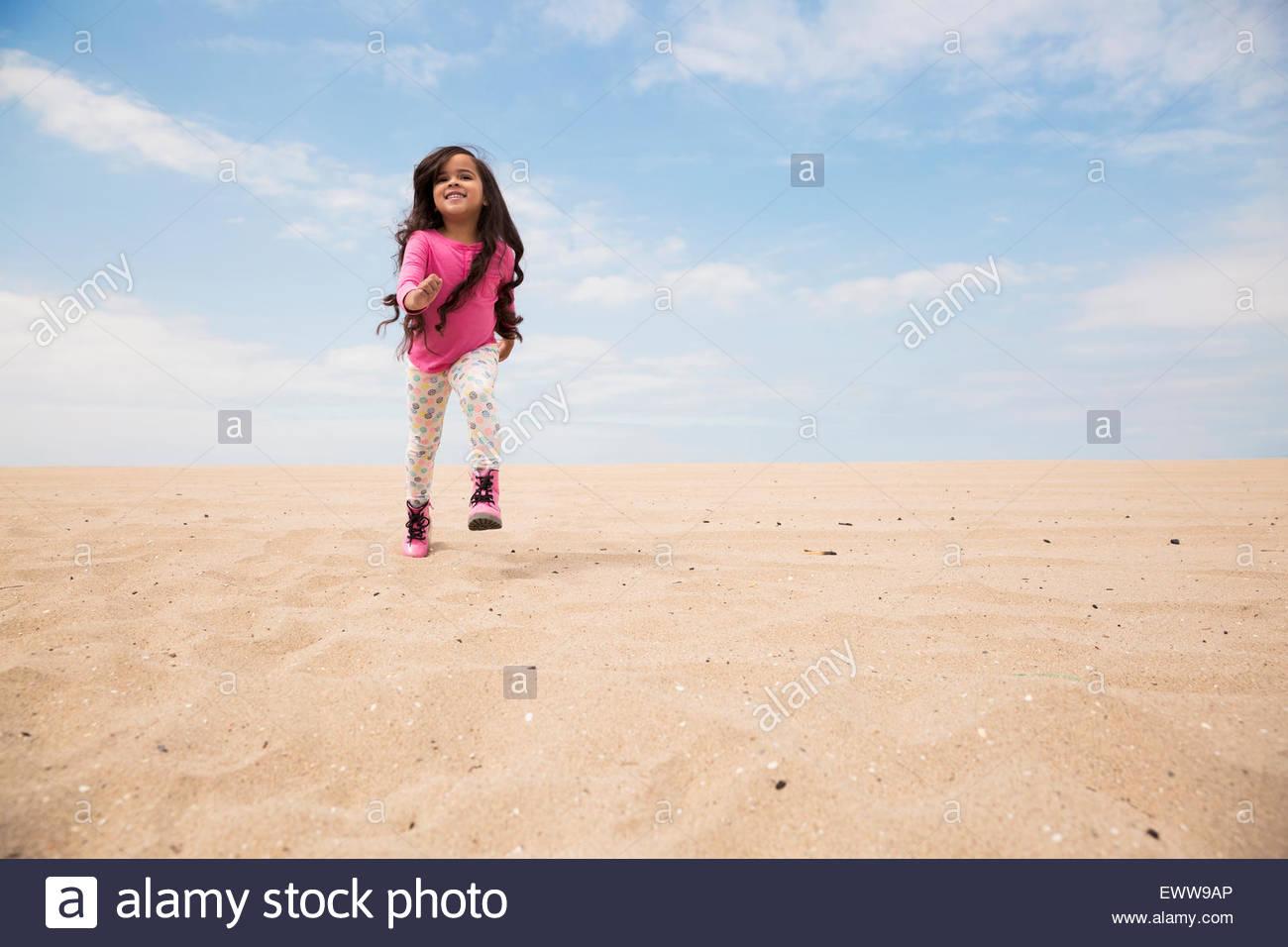 Lächelnde Mädchen lange Haare laufen am Strand Hang Stockbild
