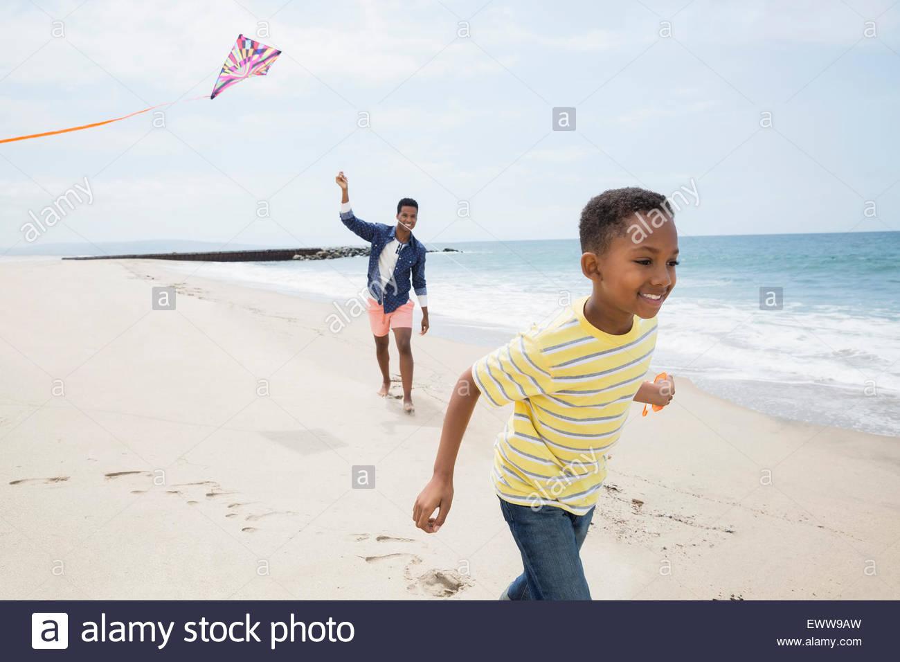 Vater und Sohn fliegen Kite am Strand Stockbild
