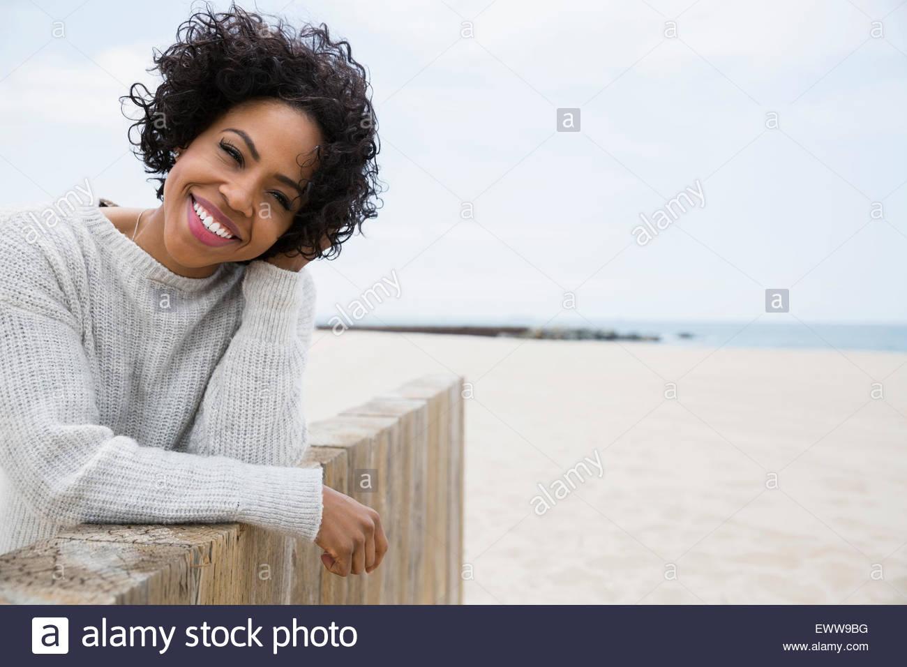 Porträt Frau lockiges schwarzes Haar Strand Wand Lächeln Stockbild